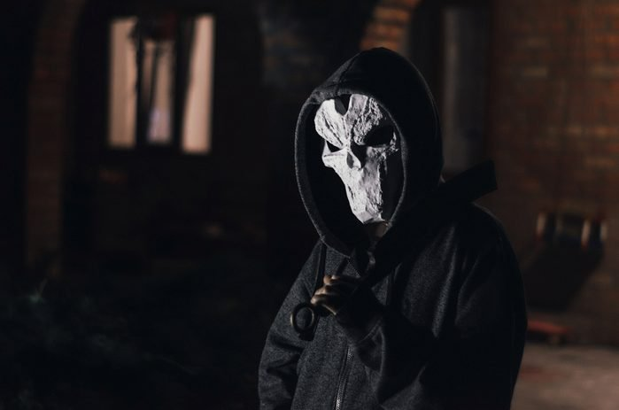man in a hood and skull mask with a big machete on a black background