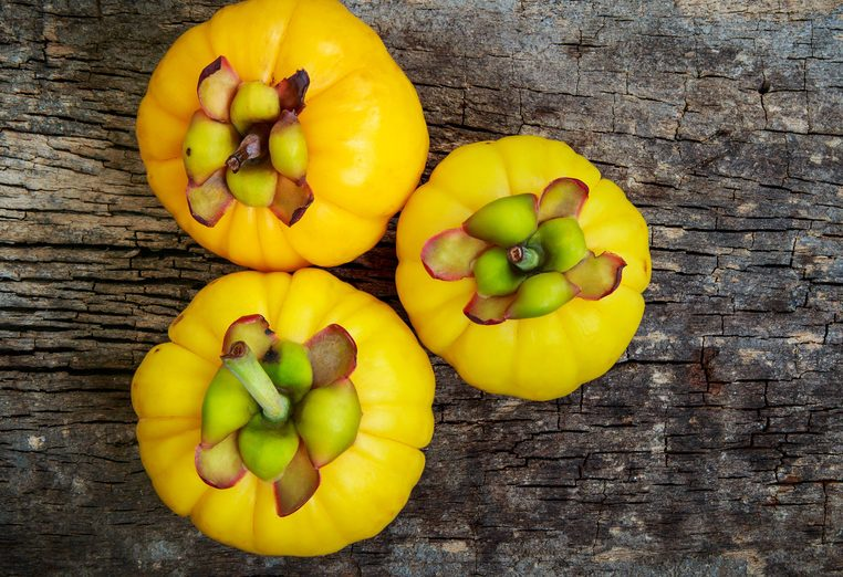 Top view. Three garcinia cambogia fruit on wood background and free form copy space. Garcinia atroviridis is a spice plants and hydroxy citric acids (HCA) for good health.