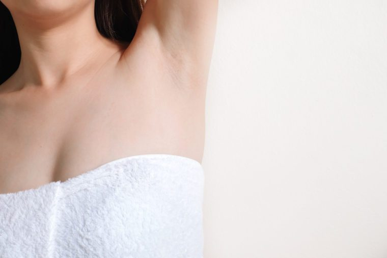 Closeup of a beautiful young woman showing her smooth armpit isolated on white background. Girl holding her arms up and showing clean underarms.