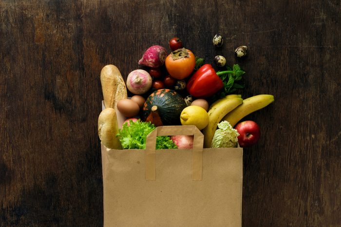 Paper bag of different health food on dark wooden background. Top view. Flat lay