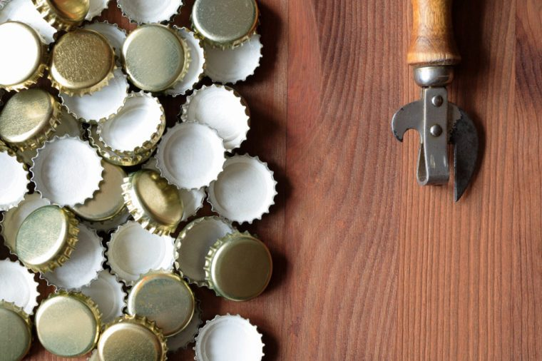 Old opener near lot of bottle caps on wooden background
