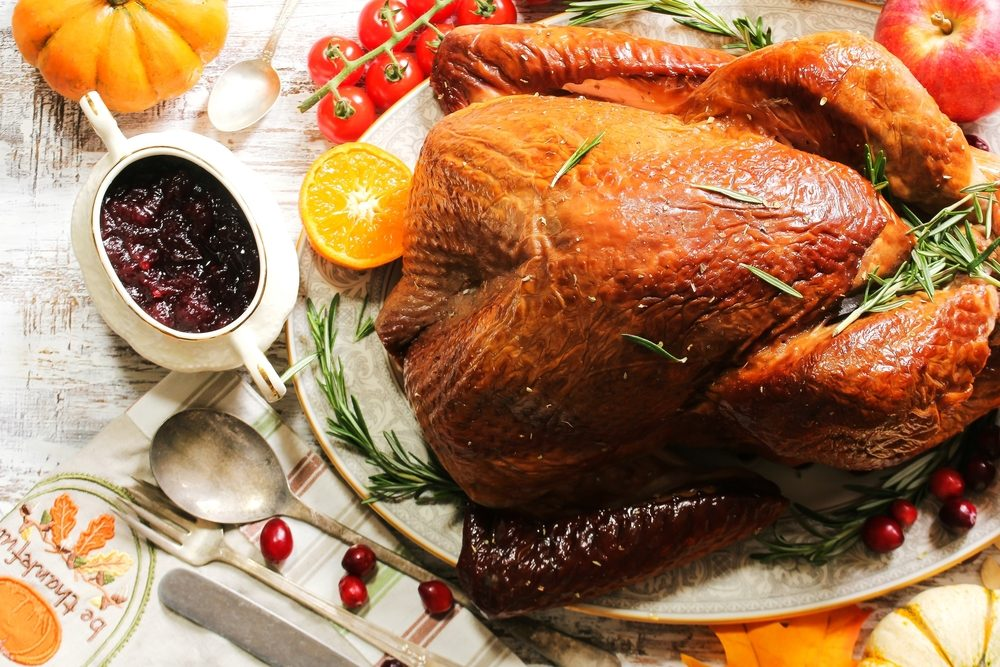 Overhead view of Homemade Thanksgiving Turkey with all sides vegetables fruits on festive white background