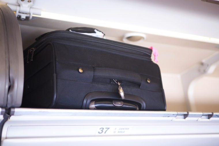 Passenger baggage stow in the cabin overhead bin in the commercial airplane, selective focus.