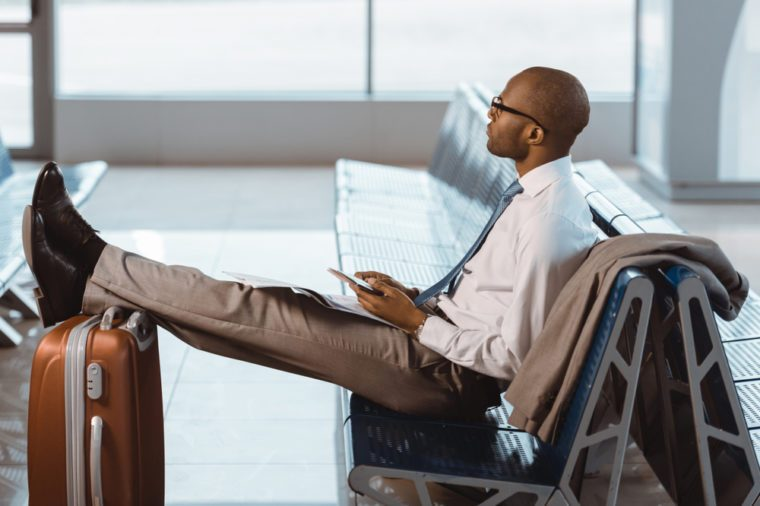 businessman using smartphone while waiting for flight at airport lobby