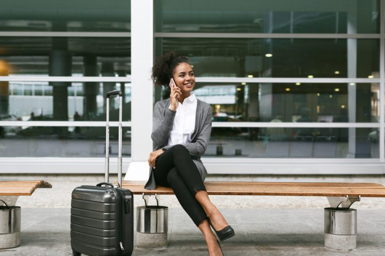 Smiling businesswoman sitting on bench and talking on mobile phone at airport terminal