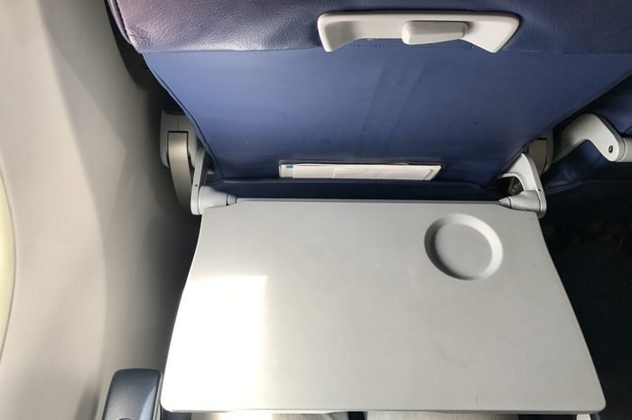 Airplane cabin is all white. All its decorations are necessary stuffs and safety. The gray Tray table for passenger in plane.