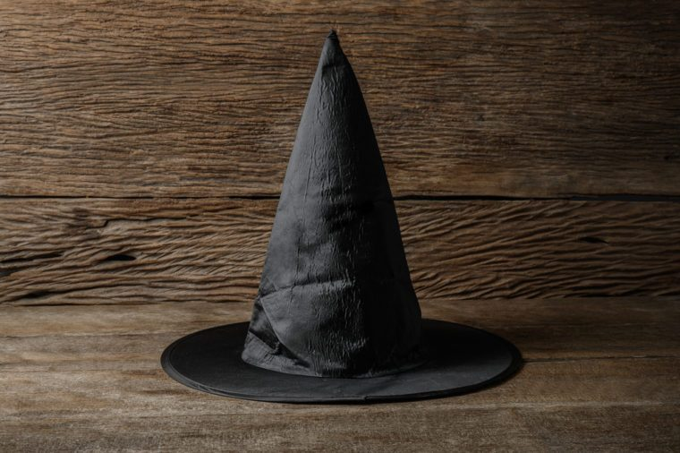 Witch hat on wooden table. Halloween holiday concept