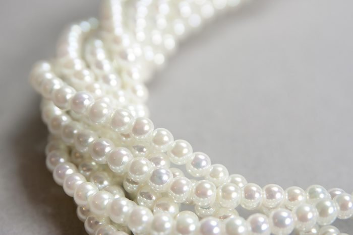 twisted strands of white pearls on a gray background