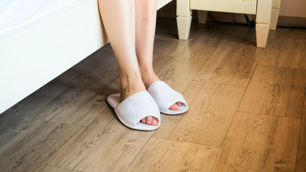 Closeup photo of female feet wearing white hotel slippers at bed
