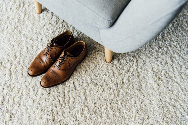 close up of leather oxford shoes on carpet near textile armchair