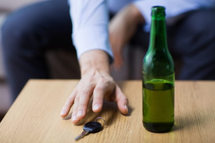 alcohol abuse, drunk driving and people concept - close up of beer bottle and male driver hand taking car key from table