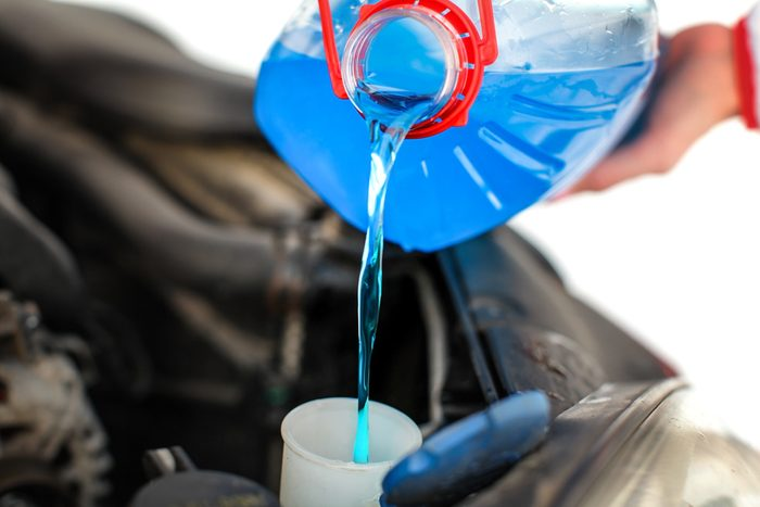 Woman pouring blue antifreeze liquid into dirty car.