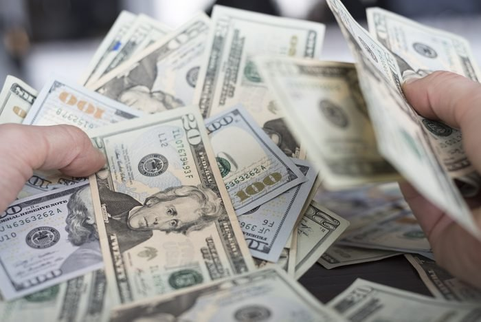 Hands grabbing a big pile of American cash money