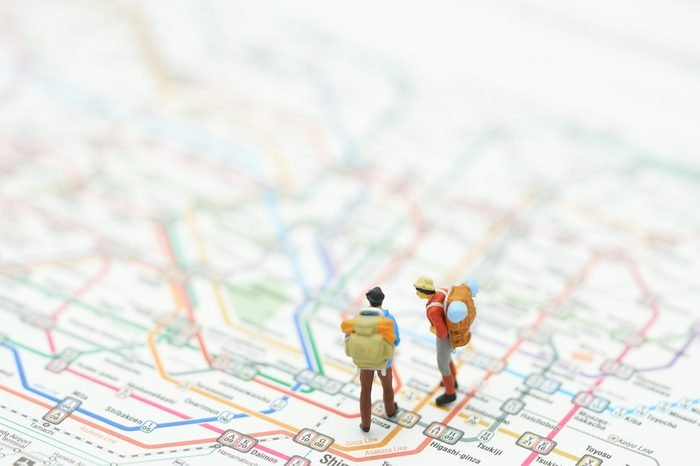 Miniature 2 people stand on a map of the subway lines in Japan. as background travel concept with copy space.