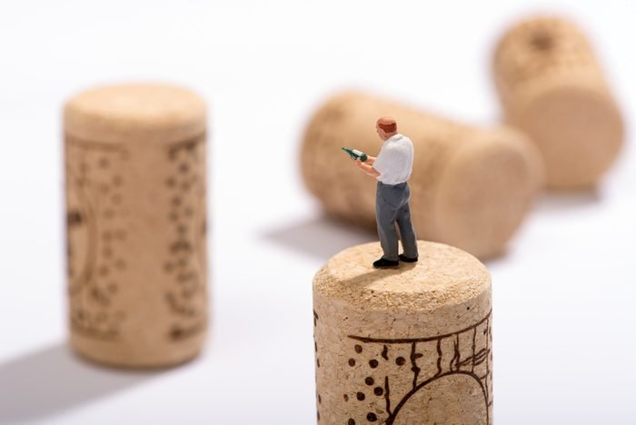 Miniature figure of a sommelier or wine expert standing on a cork looking at a bottle in his hand for pairings at a restaurant