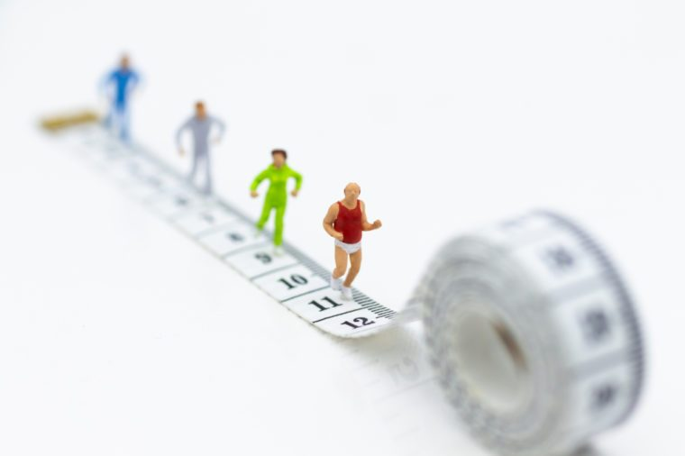 Miniature people running on waistline . Image use for healthy , exercise concept.