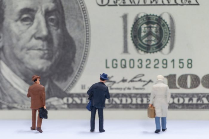 Selective focus miniature business people saving money for stock investment with dollar, financial conception.