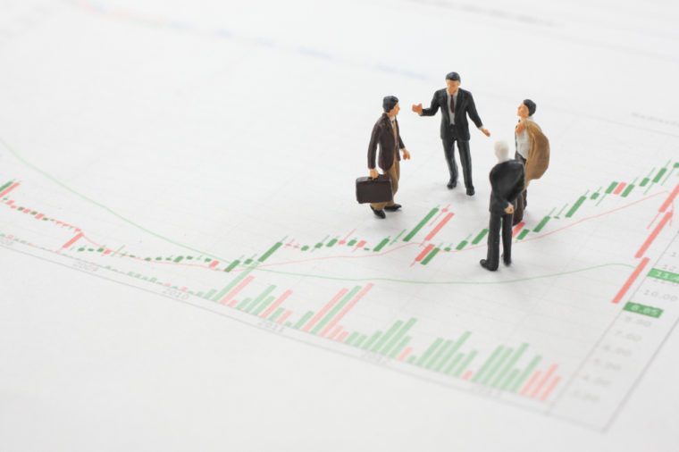 Miniature figure Businessmen standing on the report graph of business direction strategy and teamwork concept