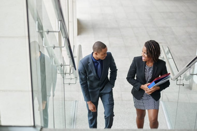 African-American business couple walking up the stairs and talking