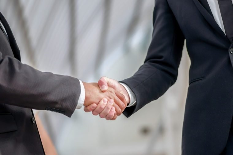 Welcoming business partners Handshake. Two successful businessman sitting at the table looking at each other shaking hands