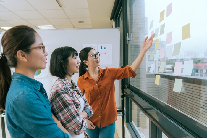 smiling beautiful woman manager showing idea for her designer team and stick many memo paper on office glass window wall during meeting.