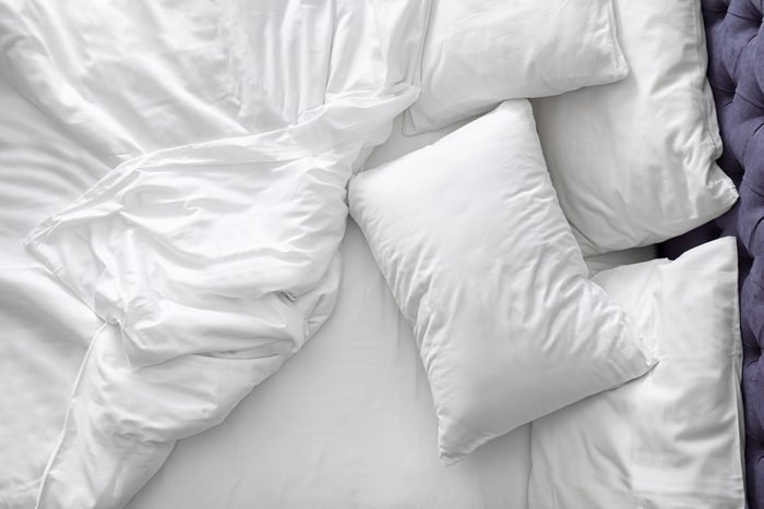 Comfortable bed with white linen at home