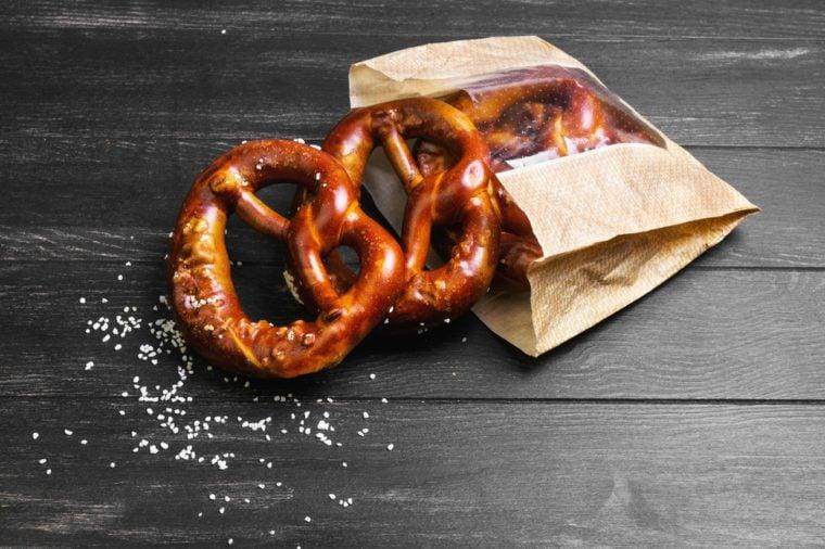 Fresh German pretzels with sea salt close-up, paper packaging for pretzels on dark black board background