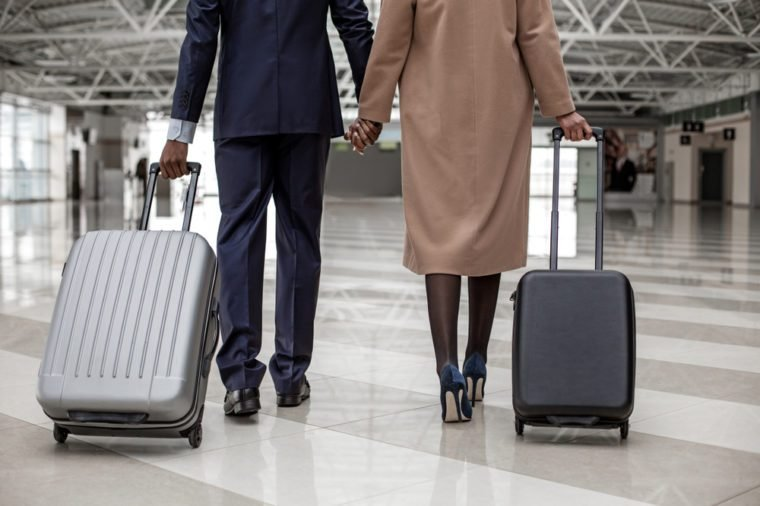 Close-up back view of legs of enamored businesswoman and businessman are going along airport lounge. They are holding hands while carrying their suitcases to departure area