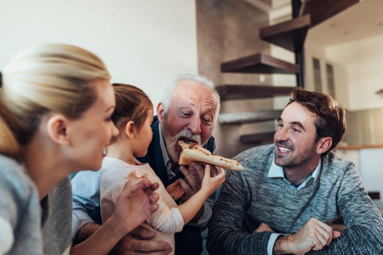 Three generation family eating pizza together