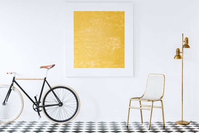 Old-fashioned bike in a minimalist, hipster living room interior with golden decor and an abstract oil painting on a white wall
