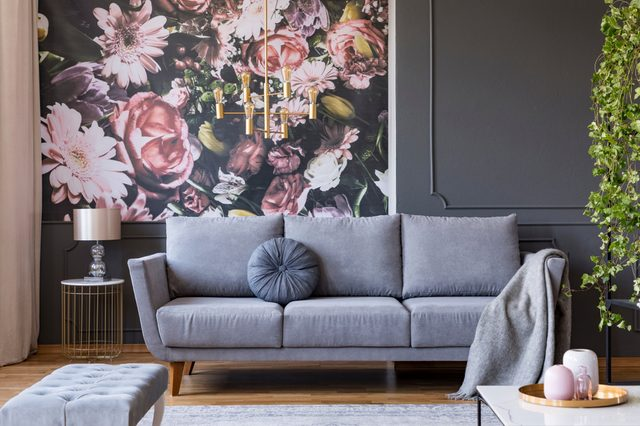 Blanket on grey couch in living room interior with flowers wallpaper and lamp on table. Real photo