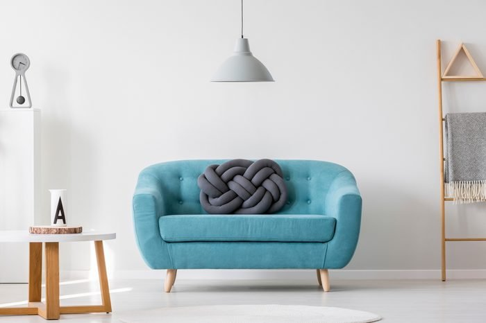 Knot pillow on turquoise sofa in living room interior with gray lamp, ladder and wooden table