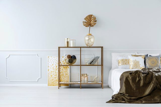 Gold leaf in vase on a shelf against white molding wall in sophisticated bedroom interior with bed
