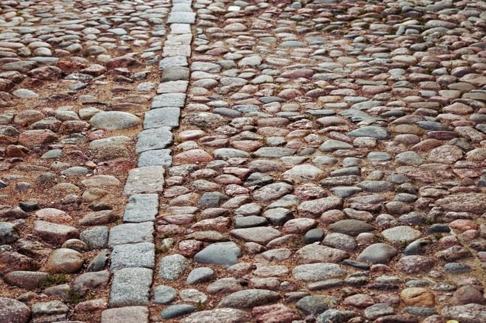 Cobblestone road. Large stones on road. Background from big stones. Road surface. Texture of stones. Selective focus.