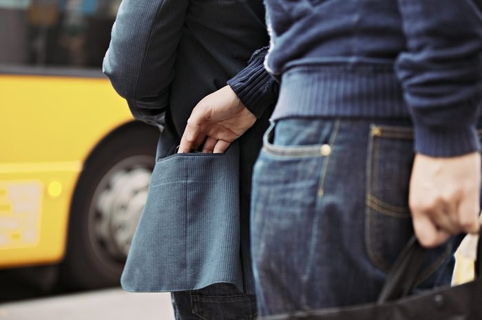 Thief stealing wallet of a man walking on the street. Pickpocketing on the street during daytime