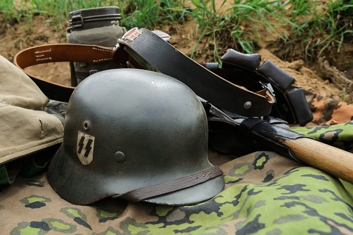 German helmet and outfit from the time of the Second World War lie in a trench on a camouflage raincoat