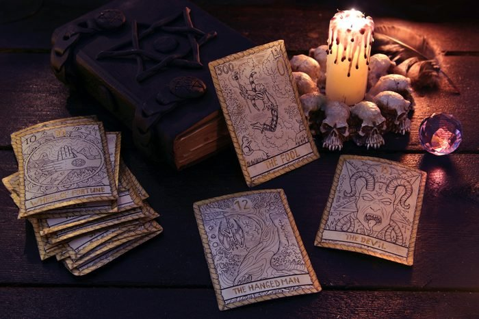 The tarot cards with crystal, candle and book. Halloween and magic still life, fortune telling seance or black magic ritual with mysterious occult and esoteric symbols, divination rite