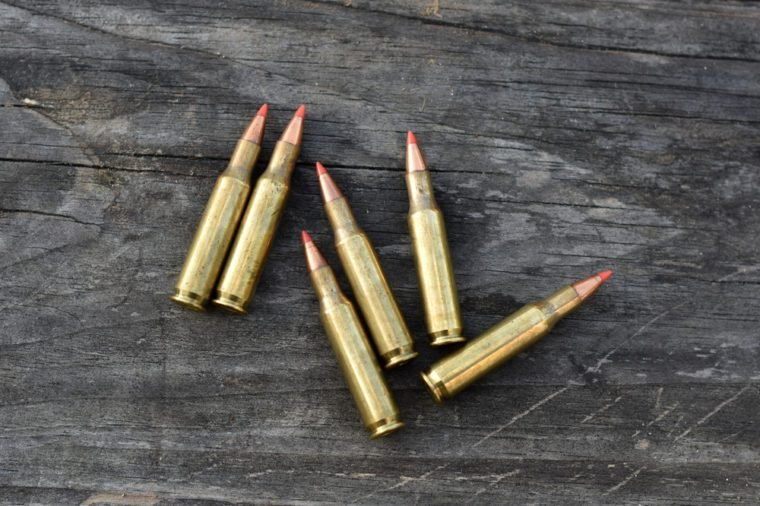 six of 223 bullet lay on wooden backgound