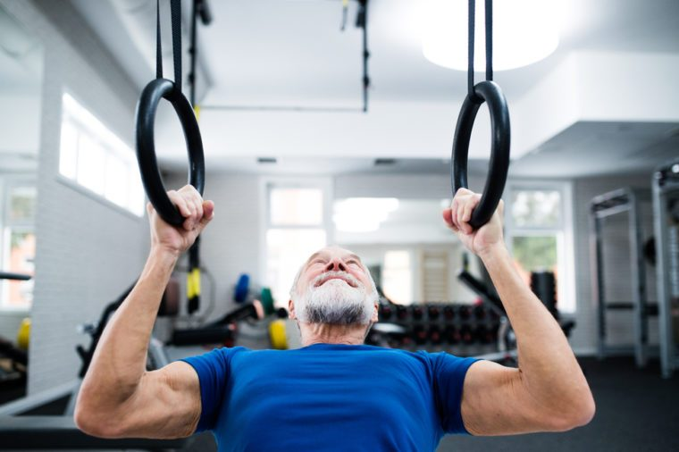 Senior man in gym working out on gymnastic rings