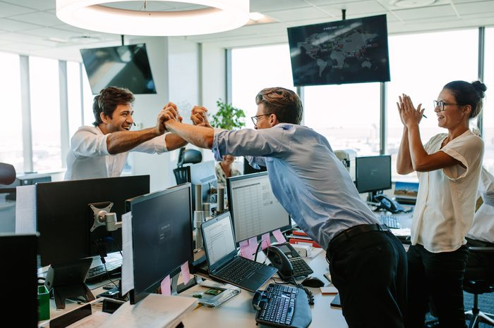 Business team cheering at good news as they congratulate each other on a success. Colleagues high fiving and clapping, celebrating success.