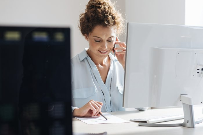 Young businesswoman using a mobile phone while working on a desktop computer at the modern office space.