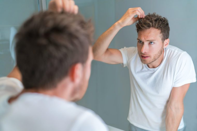 Hair loss man looking in bathroom mirror styling hairstyle with gel or checking for hair loss or grey hairs. Unhappy male health problem.