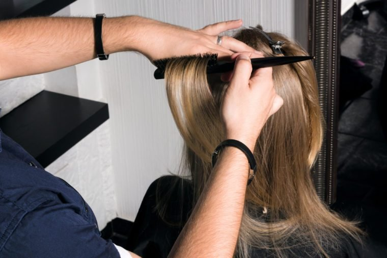 Young woman doing hair styling in the salon. The hairdresser increases the volume at the roots of the hair.
