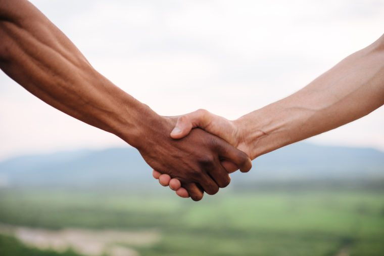 Close-up of mixed race couple holding hands on the green mountain background