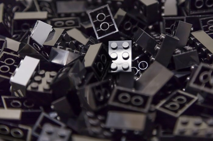 Pile of black color building blocks with selective focus and highlight on one particular block using available light.