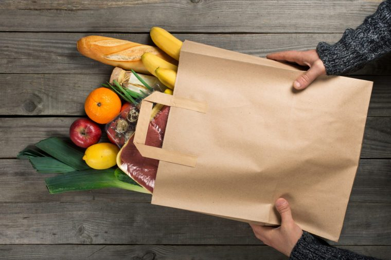 Man holding bag full of different healthy food on wooden kitchen table, top view