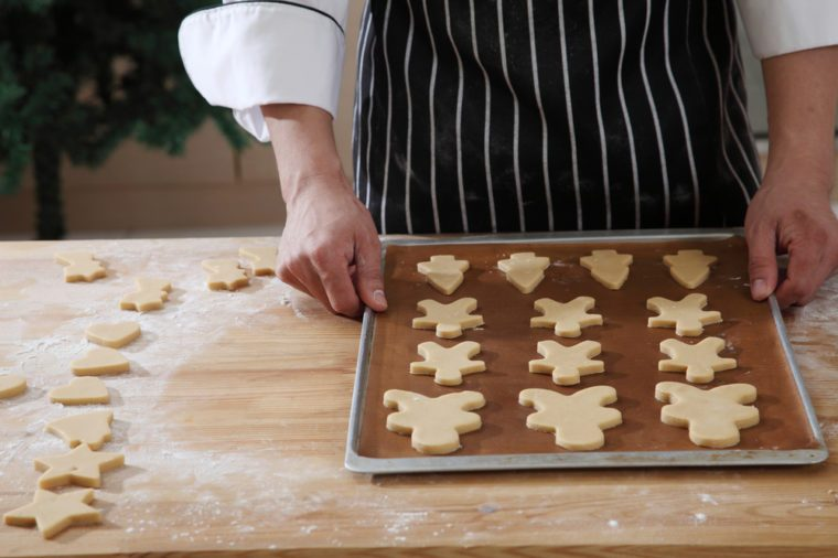 chef holding a tray raw cookies