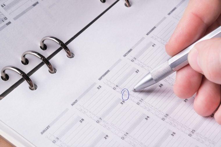 silver pen writing on open business agenda calendar