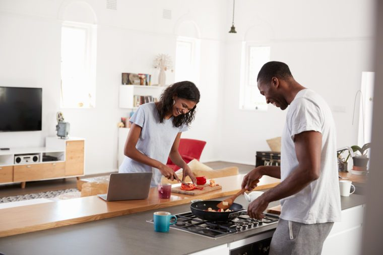 Couple Preparing Meal Together In Modern Kitchen