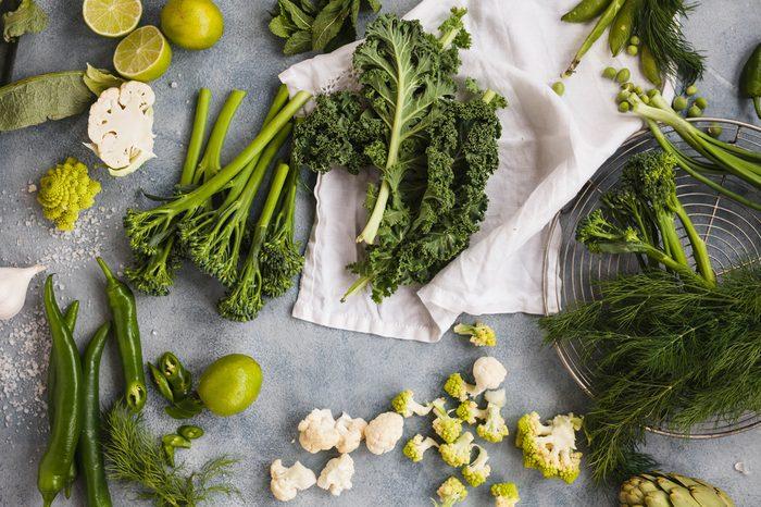 Assorted green vegetables kale leaves tenderstem broccoli peppers cauliflowers pea dill onion asparagus spring vegetables overhead